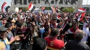 Iraqis wave their national flag as they demonstrate in Baghdad's Tahrir Square on April 16, 2016, against the Sadrist Movement, sectarian quotas and government corruption.     / AFP / SABAH ARAR        (Photo credit should read SABAH ARAR/AFP/Getty Images)